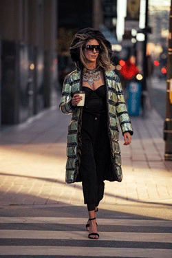 Woman walking on urban sidewalk holding a coffee cup and wearing a winter coat lined with Canadian 20 dollar bills.
